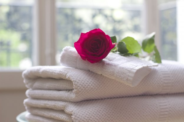 An image of hotel towels and a rose